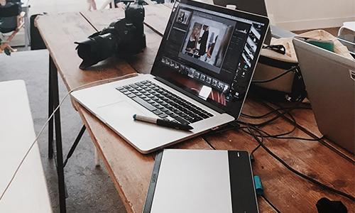 Spiegelreflexkamera neben Laptop mit Grafiktablet und Zeichenstift.