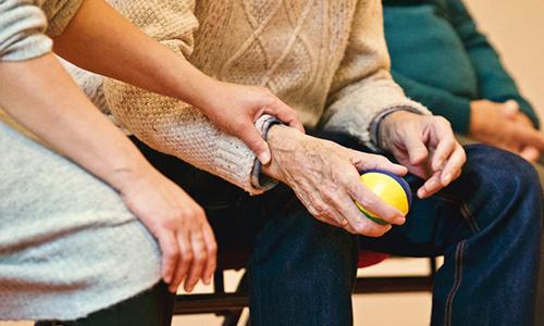 Person hält älterem Menschen die Hand.